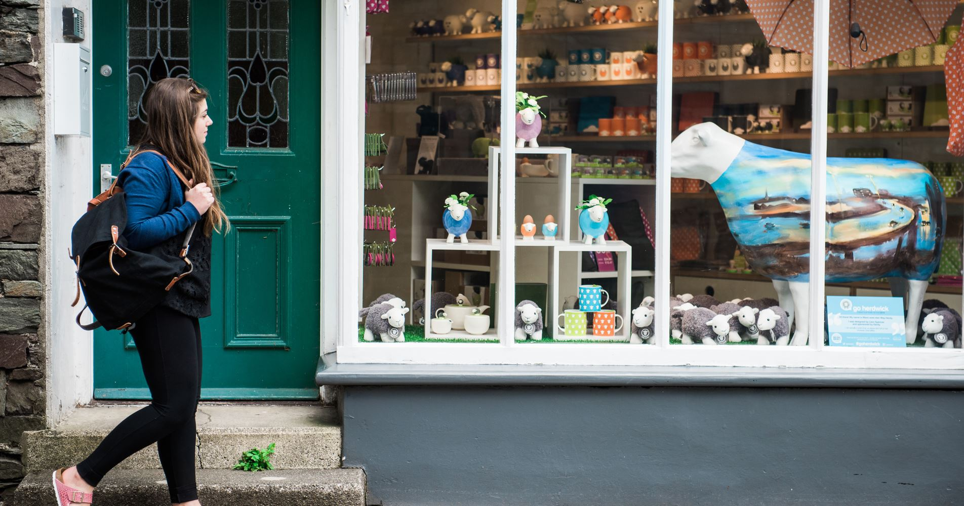 A young woman with a backpack and sandals walks past a colourful gift shop full of bright mugs, local animal toys and paintings
