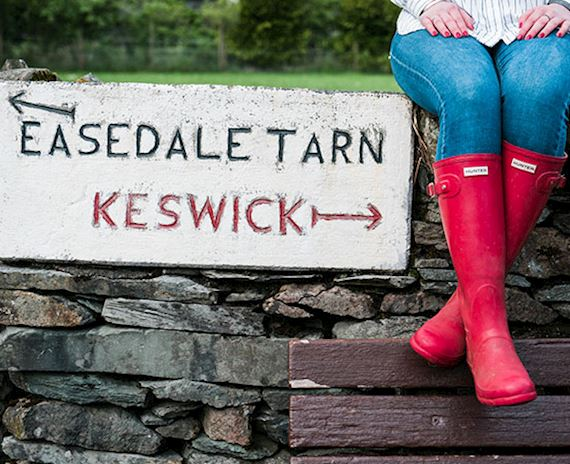 Photo of a sign pointing to Easedale Tarn one way and Keswick the other, with a woman sat in red wellies on top of the fence so only her wellies and legs are visible next to the sign in the countryside