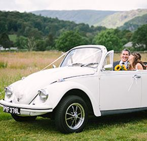 A happy couple in a classic white Beetle smile after just getting married at Daffodil Hotel