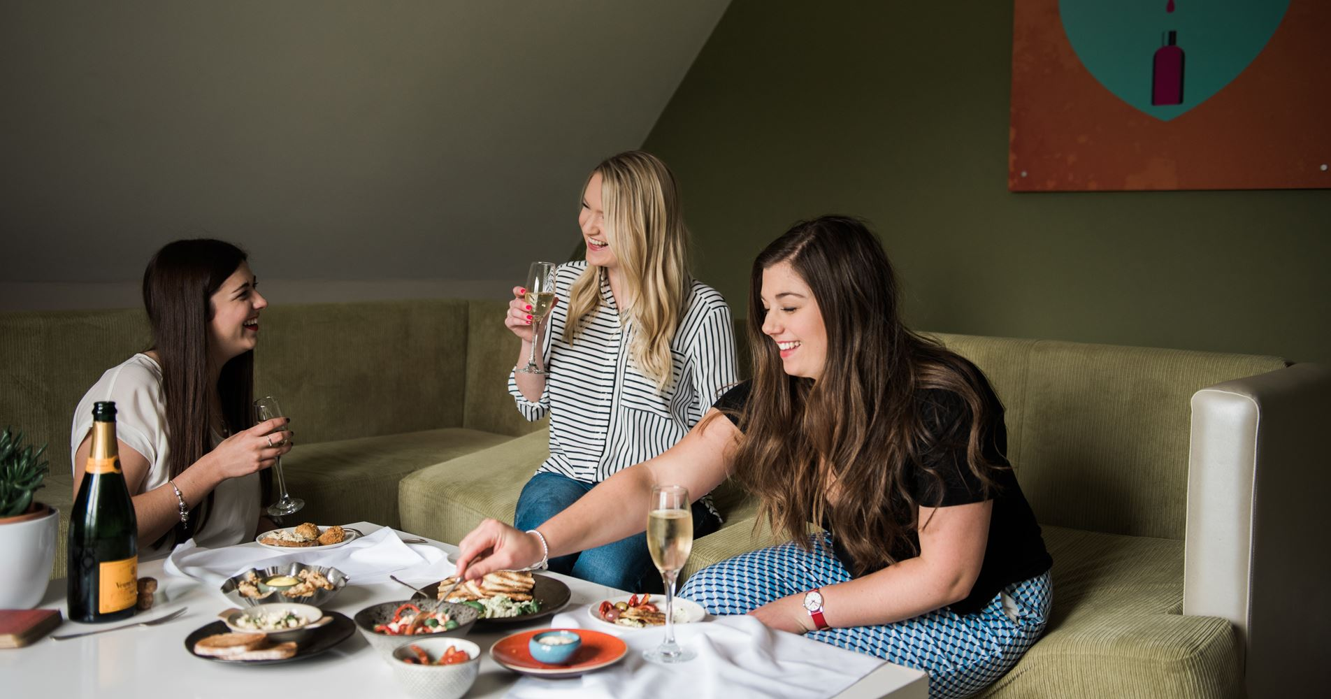 Three young women laugh on a sofa together whilst enjoying a table spread of appetisers and a bottle of bubbly