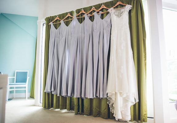Four identical lilac bridesmaids dresses hang next to a beautiful high neck cream wedding dress, against a subtle green curtain in one of the wedding suites
