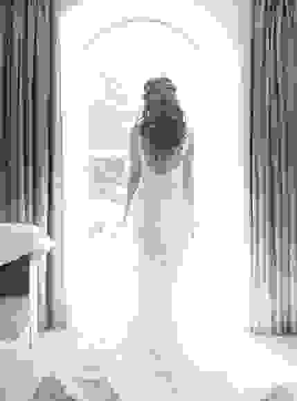 Black and white photo of a bride as she stands facing an arch window, her wedding dress trailing behind showing the intricate details of the gown