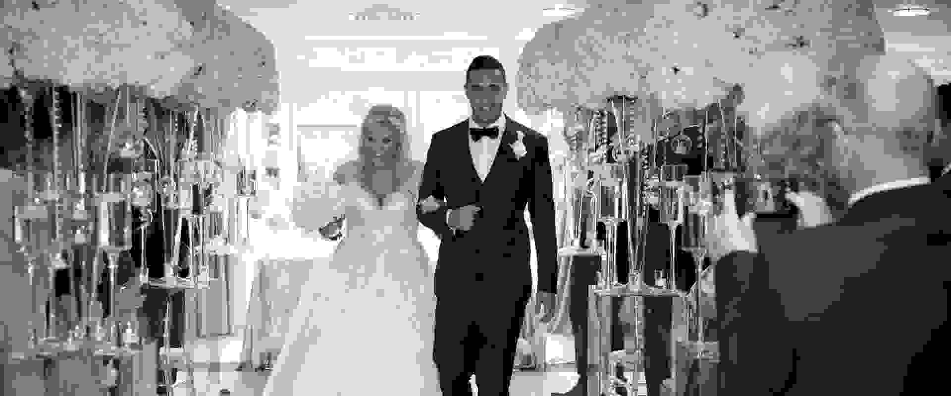 Black and white photo of a bespoke wedding, with a bride and groom walking away from the aisle after saying their vows surrounded by white confetti, bouquets and flute glasses