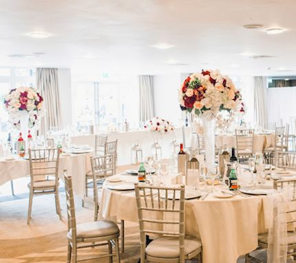 At the reception of a wedding, large circular tables with chairs are set out with beautiful white furnishings, large bouquets of flowers and wine for the guests