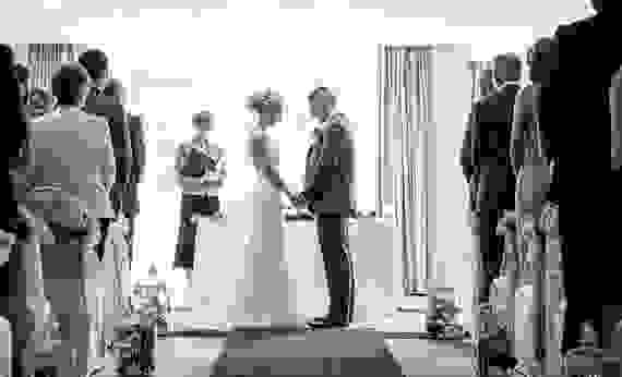 Black and white photo of a bride and groom stood at the altar, facing each other holding hands as they say their vows surrounded by family.
