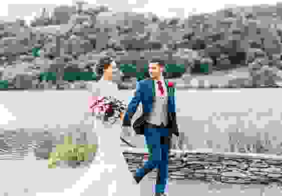 A happy bride and groom walk next to the lake after getting married, still in suit and dress.