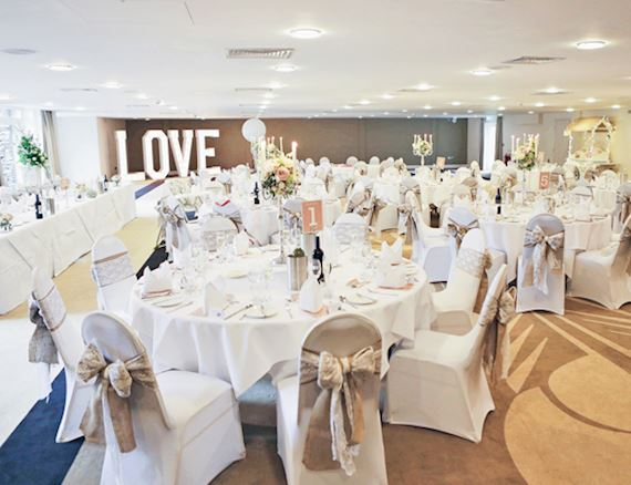 A wedding reception is set out for a meal with large round tables, beautiful furnishings and elegant white colours, with a large, lit up LOVE sign in the background