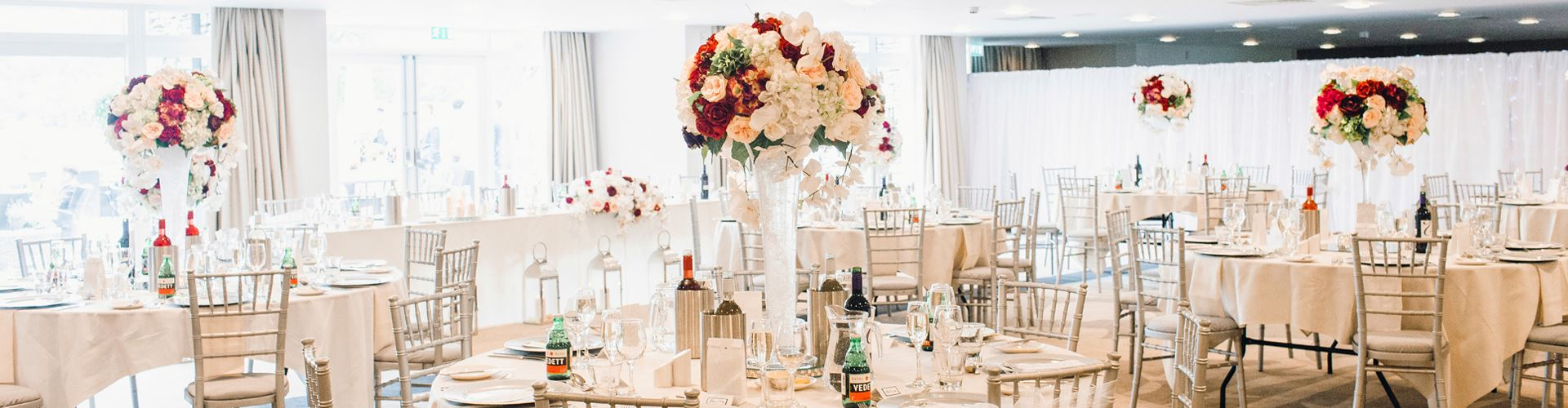 A landscape shot of a wedding reception set up with large round tables, white and red bouquets in the centre of each and elegant furnishings with place settings and bottles of wine