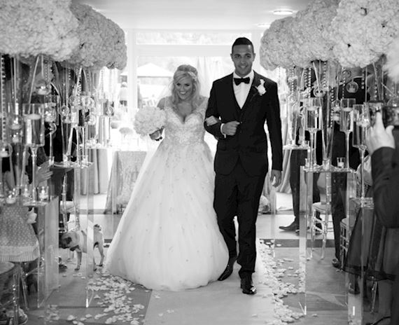 Black and white photo of a happy bride and groom walking down the aisle after getting married, surrounded by contemporary white bouquets, confetti and champagne flutes