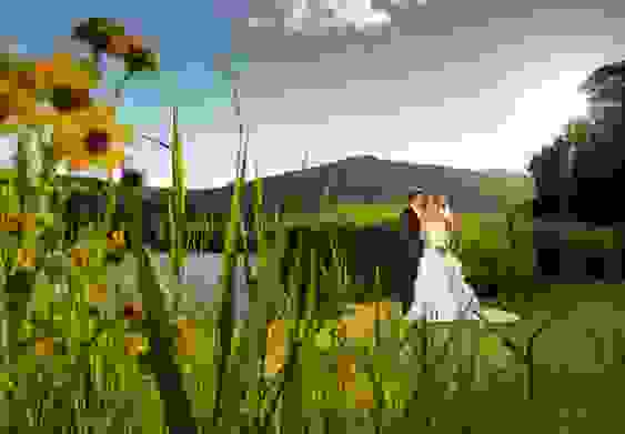 Landscape photo of a bride and groom stood together lovingly beside a lake, with the sun shining over the hills and reeds all around