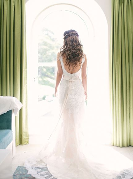 Bright and colourful shot of a bride stood facing a large arched window with her back to the camera, showing her laced gown surrounded by light