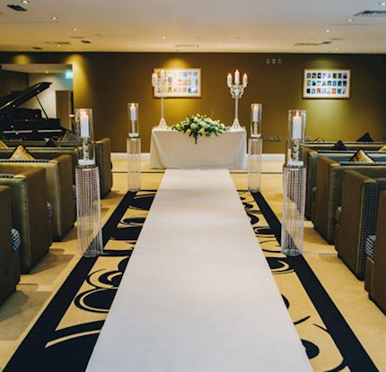 Portrait shot of the walk up to a beautiful altar, lit by candles with a warm gold theme and elegant furnishings