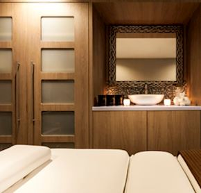 Luxury spa beds, with fresh towels ready for the next treatment with contemporary furnishings around