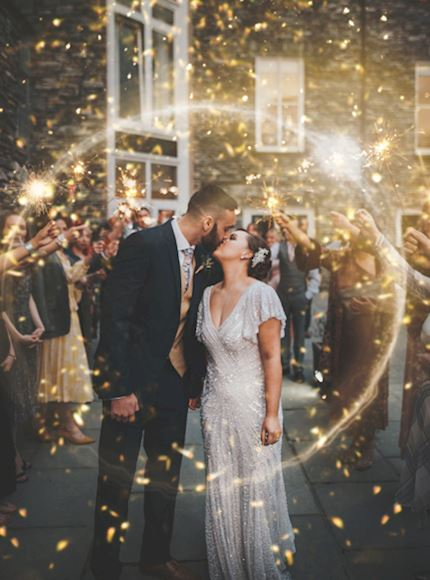 A beautiful and glamorous bride and groom stand kissing surrounded by friends and family holding sparklers after just getting married.