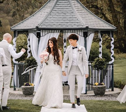 A young bride and groom walk away from the altar hand in hand after getting married, in a beautiful outdoor setting and wooden marquee draped with white ribbon